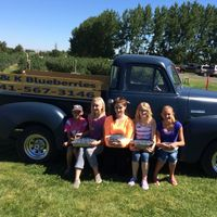 5 people hold trays of blueberries in front of an old chevy pickup