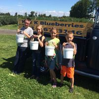 4 people hold buckets of blueberries in front of an old chevy pickup